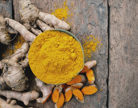 Whole Turmeric roots and a bowl of bright Turmeric powder sit on a wooden surface.